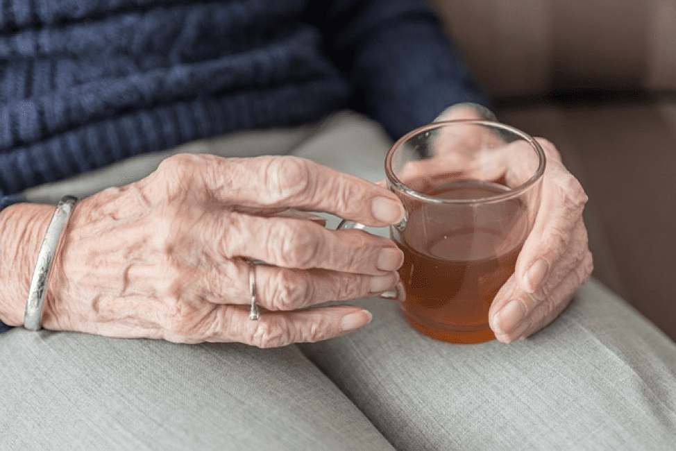 Hands of senior age woman with cup of tea